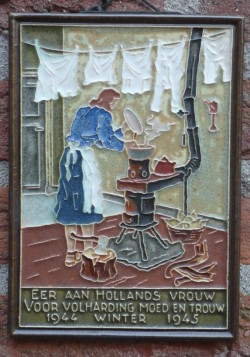 Tribute to Dutch Women of the Winter of Hunger. Photo by Peter de Wit (2008). Tile made by 'De Porceleyne Fles' in Delft, Netherlands. PD-CCA 2.0. Wikimedia Commons.