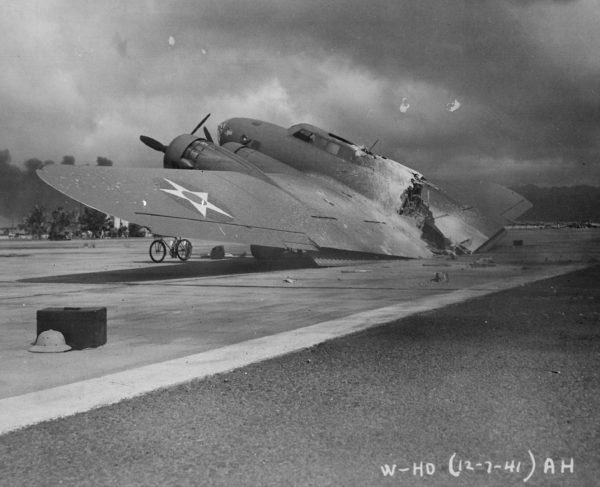 A burned B-17C aircraft rests near Hangar Number Five, Hickam Field, following the attack by Japanese aircraft. Pearl Harbor, Hawaii. Photo by anonymous (7 December 1941). Department of Defense. PD-USGOV. National Archives and Records Administration and Wikimedia Commons.