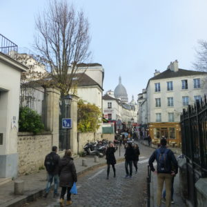 View of Rue Norvins looking SE towards Sacré-Cœur. Same view as image on the left. Notice the arched brick entrance in the photo on the right has been replaced with a modern entrance. Photo by Raphaelle Crevet (2016). PD-Photographer release.