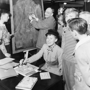 Margret & H.A. Rey signing books. Photo by anonymous (c. 1950). Wikimedia Commons.