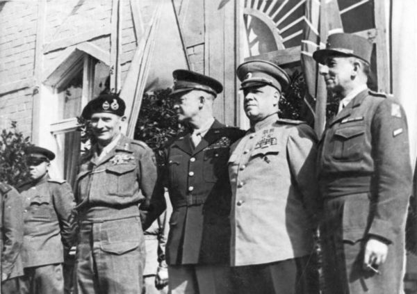 The four WWII allied military leaders: Field Marshal Bernard Montgomery (British—far left), General Dwight D. Eisenhower (American—middle left), Marshal Georgi K. Shukow (Soviet Union—middle right), and General Jean de Lattre de Tassigny (France—far right) in Berlin. Photo by anonymous (c. June 1945). Bundesarchiv, Bild 183-14059-0018/CC-BY-SA 3.0. Wikimedia Commons.