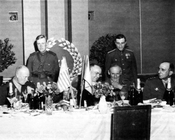 Marshal Zhukov (center) pours a toast at the 5 June 1945 meeting in Berlin. General Eisenhower (left) departed immediately after the toast (notice the scowl on the general's face). On the right are Field Marshal Montgomery (next to Zhukov) and General de Lattre de Tassigny (far right with the same scowl as Eisenhower). Photo by U.S. Army (June 1945). Courtesy of National Archives. PD-USHMM. Wikimedia Commons.