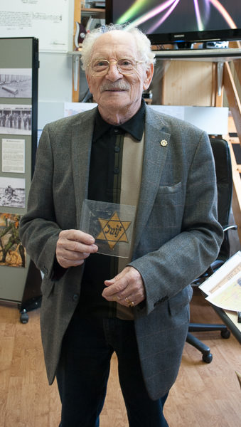 Lucien Tinandar holding the Star of David patch that belonged to and worn by his mother during the Occupation. Photo by Sandy Ross.