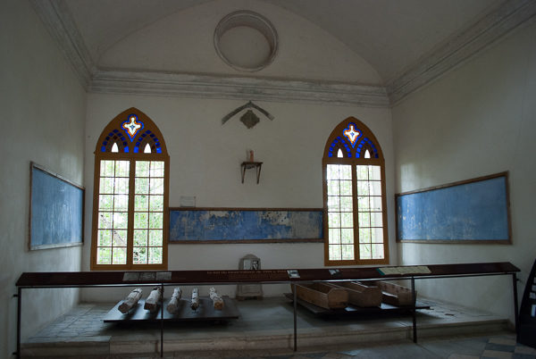 Interior of the chapel at Mont-Valérien. The five wooden stakes that the victims were tied to lie to the left while several body boxes used to transport the bodies lie to the right—in front of the two windows. Photo by Sandy Ross.