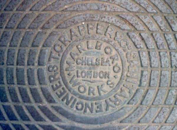 A genuine Crapper manhole cover. Photo by Patrick Mackie (1988). © Patrick Mackie and licensed under Creative Commons Attribution-ShareAlike 2.0. Wikimedia Commons.