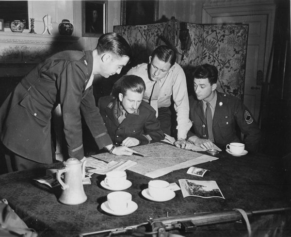 Jedburghs get instructions from briefing officer in London. Photo by anonymous (c. 1943−1944). U.S. National Archives and Records Administration. PD-Free License. Wikimedia Commons.