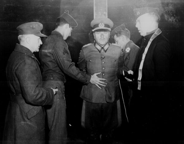 German General Anton Dostler is tied to a stake before his execution by firing squad. Guilty of ordering the execution of Allied soldiers in uniform under Hitler's Commando Order. Photo by Blomgren (1 December 1945). U.S. National Archives and Records Administration. PD-US Government. Wikimedia Commons.