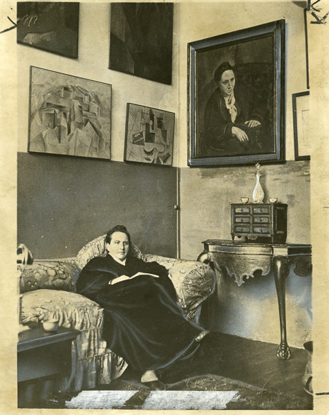 Gertrude Stein sitting on a sofa in her Paris studio. Notice her portrait painted by Picasso in the upper right corner. Photo by World Wide Photos (May 1930). PD-100+. Wikimedia Commons.