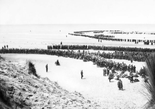 British troops line up on the beach at Dunkirk to await evacuation. Photo by anonymous (c. May 1940). American Embassy Second World War Photograph Library-Classified Print Collection. PD-United Kingdom Government. Wikimedia Commons.