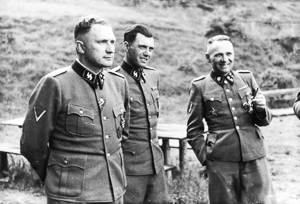 Three SS officers socialize on the grounds of the SS retreat outside of Auschwitz. From left to right they are: Richard Baer (Commandant of Auschwitz), Dr. Josef Mengele, and Rudolf Hoess (former commandant of Auschwitz). Photo by Karl-Friedrich Höcker (c. 1944). PD-Release by Polish Government. Wikimedia Commons.