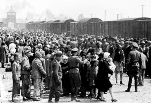 """Selection"" process of Hungarian Jews on the ramp at Auschwitz II-Birkenau. The majority of the men, women, and children would be dead within hours. Notice the entrance building in the background (left). Photo by likely either Ernst Hoffmann or Bernhard Walter of the SS (c. May/June 1944). Yad Vashem – The Auschwitz Album. PD-Expired copyright and author is anonymous. Wikimedia Commons."