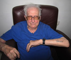 Jerzy Kamieniecki (b. 1920), prisoner of Auschwitz II-Birkenau, Matthausen, and Gusen shows tattoo with camp number. Photo by Jacek Proszyk (2010). Creative Commons Attribution-Share Alike 4.0 International. Wikimedia Commons.